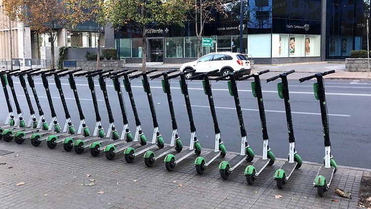A row of e-scooters on a city street